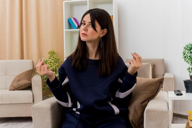 Молодая красивая кавказская женщина, сидящая на кресле в дизайнерской гостиной, смотрит и делает денежный жест