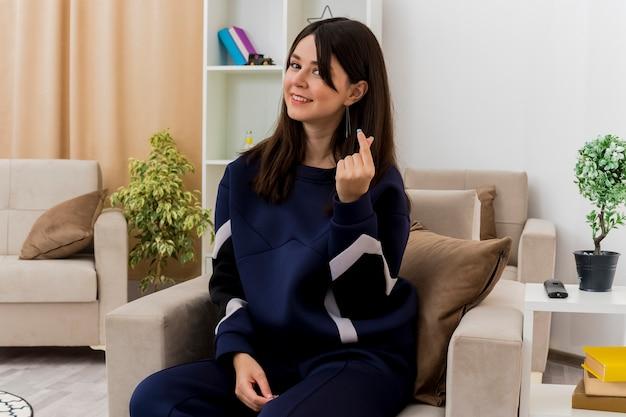 Молодая симпатичная кавказская женщина, сидящая на кресле в дизайнерской гостиной, улыбается и делает денежный жест