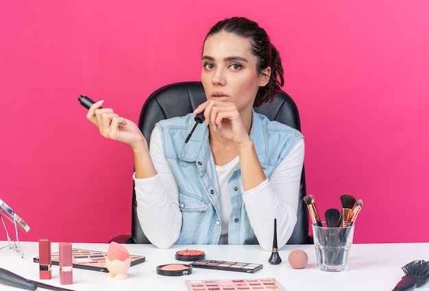 Giovane donna abbastanza caucasica seduta al tavolo con strumenti per il trucco che tengono mascara isolato su parete rosa con spazio di copia