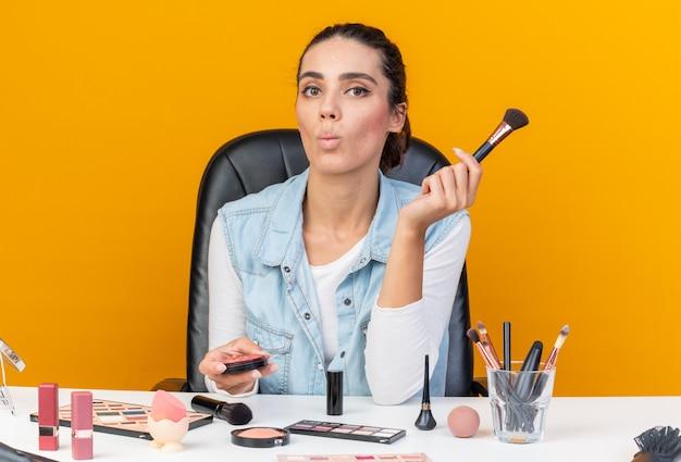 Giovane donna abbastanza caucasica seduta al tavolo con strumenti per il trucco che fa la faccia di pesce che tiene fard e pennello per il trucco isolato sulla parete arancione con spazio di copia