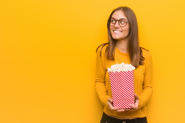 Young pretty caucasian woman smiling confident and crossing arms, looking up. she is eating popcorns.