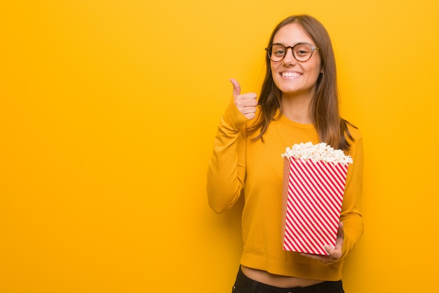 Young pretty caucasian woman smiling and raising thumb up. she is eating popcorns.