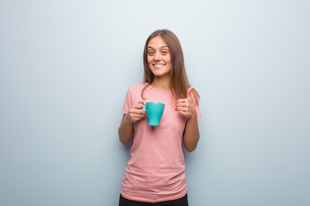 Young pretty caucasian woman smiling and raising thumb up. she is holding a mug.