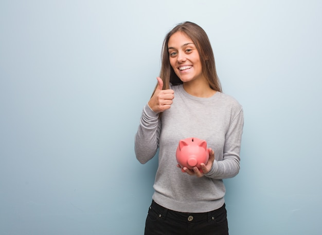 Young pretty caucasian woman smiling and raising thumb up. she is holding a piggy bank.