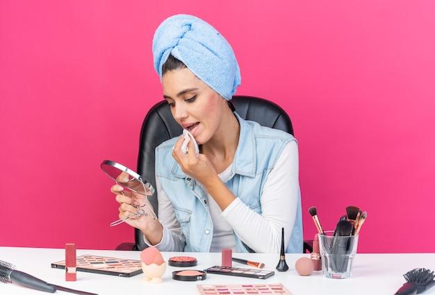 Giovane donna abbastanza caucasica con i capelli avvolti in un asciugamano seduto al tavolo con strumenti per il trucco che tengono e guardando lo specchio asciugandosi la bocca con un tovagliolo isolato sulla parete rosa con spazio di copia