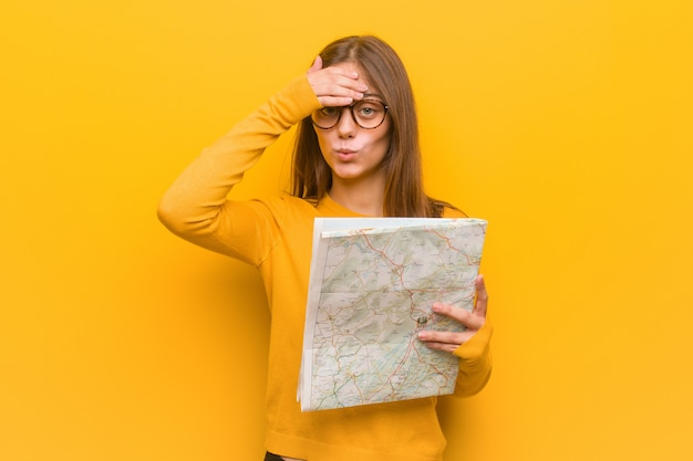 Young pretty caucasian woman worried and overwhelmed. she is holding a map.
