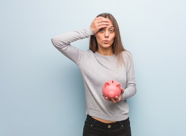 Young pretty caucasian woman worried and overwhelmed. she is holding a piggy bank.
