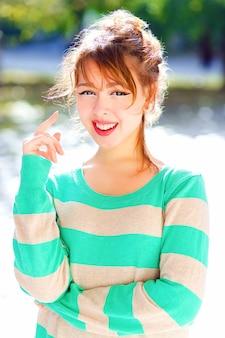 素敵な夏の日に市の公園でポーズをとる若いかなり陽気な十代のアジアの女の子は、陽気な遊び心のある気分、笑顔で楽しんで、カジュアルなストライプのセーターを着ています。明るいライフスタイルの肖像画。