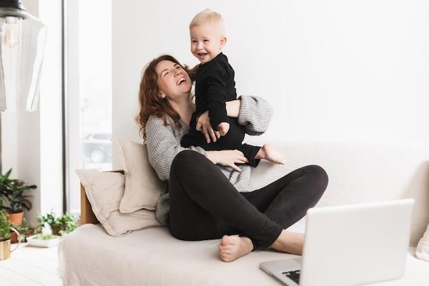 彼女の小さな笑う息子と一緒に楽しく遊んでソファに座っている若いかなり陽気な女性