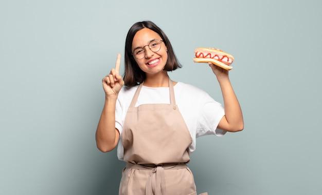 Young pretty chef woman holding hotdog