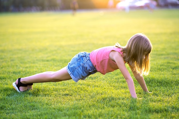 Young pretty child girl exercising on green grass lawn on warm summer evening.