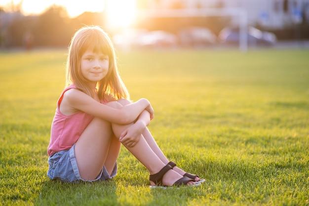 따뜻한 여름날 야외에서 신선한 녹색 잔디 잔디밭에 앉아 있는 예쁜 어린 소녀입니다.
