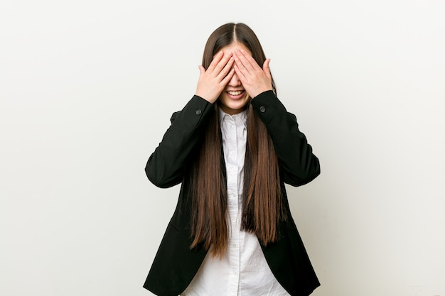 Young pretty chinese business woman covers eyes with hands, smiles broadly waiting for a surprise.
