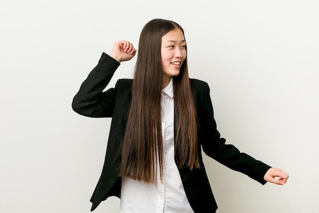 Young pretty chinese business woman dancing and having fun.