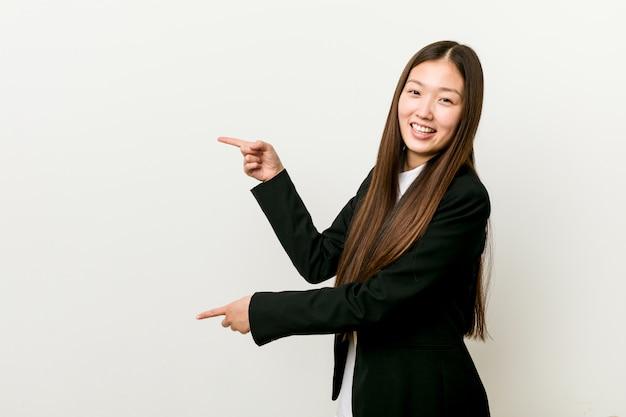 Молодая милая китайская бизнес-леди возбужденная указывать с указательными пальцами прочь.