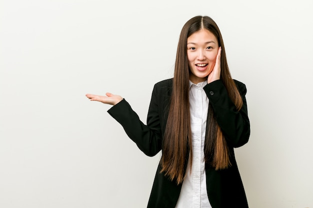 Young pretty chinese business woman holds copy space on a palm, keep hand over cheek. amazed and delighted.