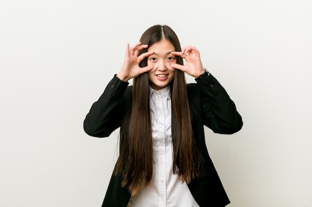 Young pretty chinese business woman keeping eyes opened to find a success opportunity.