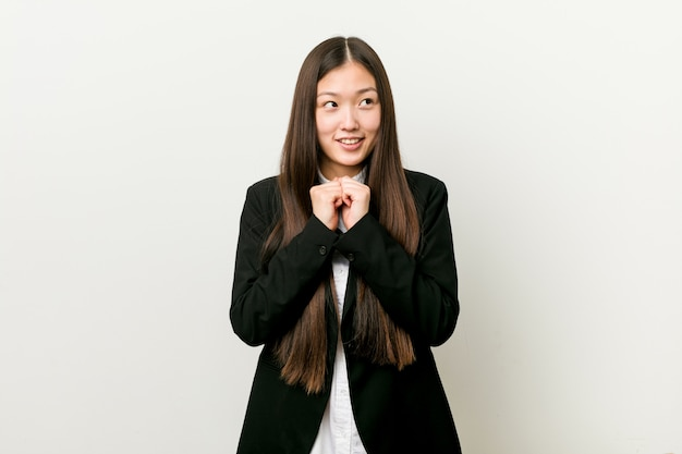 Young pretty chinese business woman keeps hands under chin, is looking happily aside.