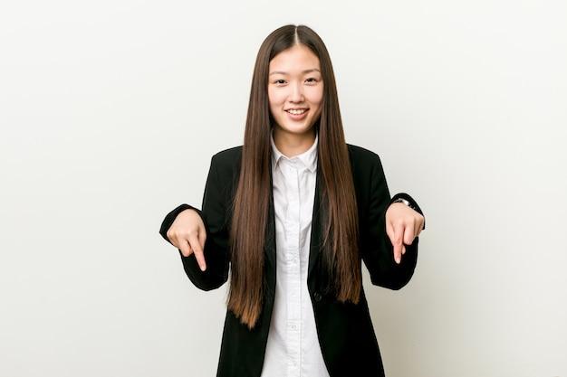 Молодая милая китайская бизнес-леди указывает вниз с пальцами, положительным чувством.