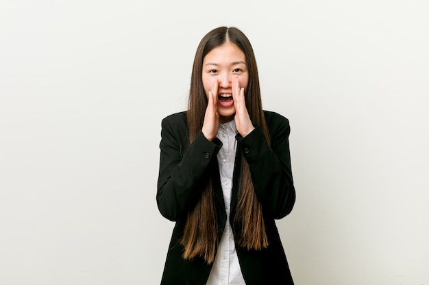 Young pretty chinese business woman shouting excited to front.