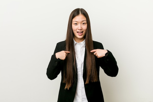 Young pretty chinese business woman surprised pointing with finger, smiling broadly