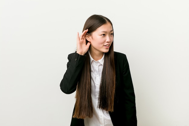 Young pretty chinese business woman trying to listening a gossip.