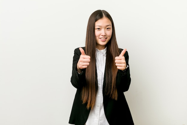 Young pretty chinese business woman with thumbs ups, cheers about something, support and respect concept.