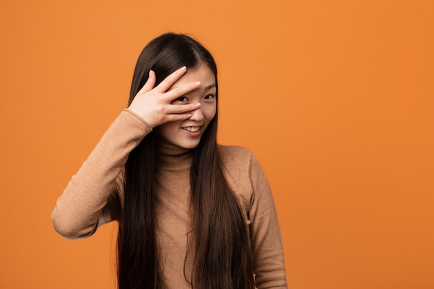 Young pretty chinese woman blink at the camera through fingers, embarrassed covering face.