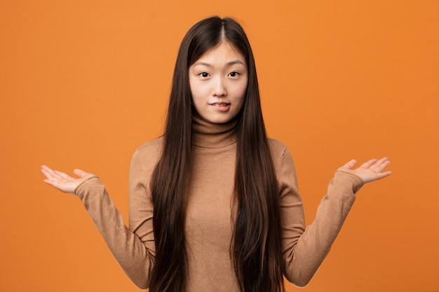 Young pretty chinese woman confused and doubtful raising him hands to hold a copy space.