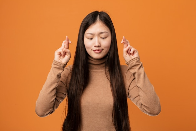 Young pretty chinese woman crossing fingers for having luck