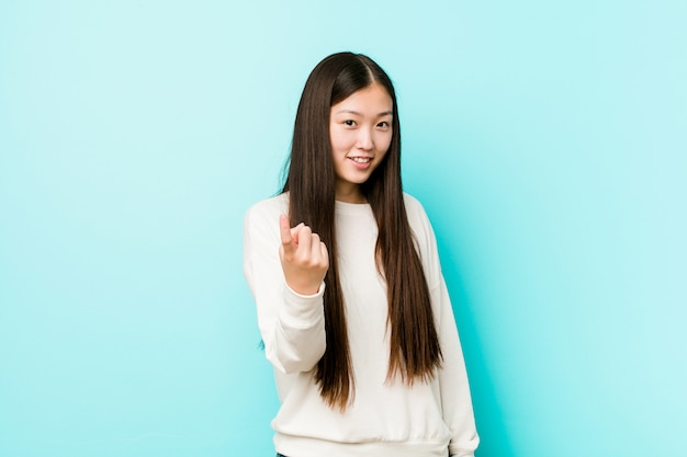 Young pretty chinese woman pointing with finger at you as if inviting come closer.