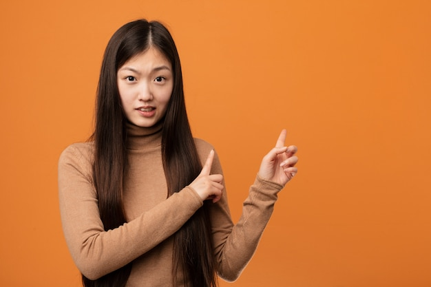 Young pretty chinese woman shocked pointing with index fingers to a copy space.