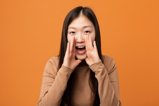 Young pretty chinese woman shouting excited to front.