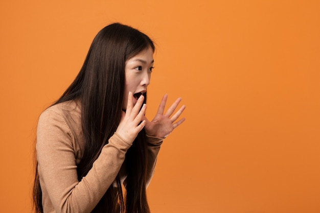 Young pretty chinese woman shouts loud, keeps eyes opened and hands tense.
