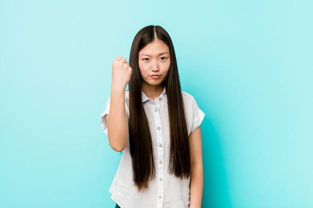 Молодая милая китайская женщина показывая кулак