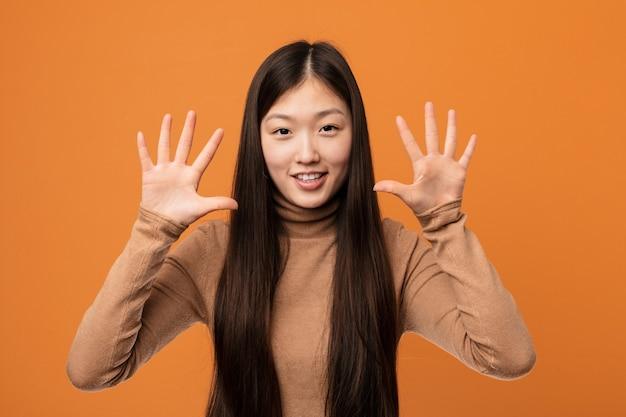 손으로 번호 10을 보여주는 젊은 꽤 중국 여자.
