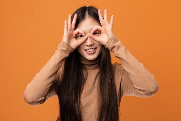 눈에 괜찮아 기호를 보여주는 젊은 예쁜 중국 여자