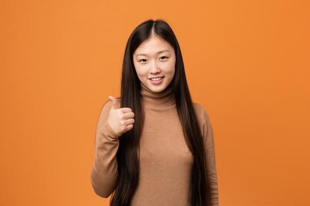 웃 고 엄지 손가락을 올리는 젊은 예쁜 중국 여자