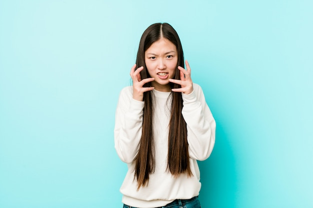 Young pretty chinese woman upset screaming with tense hands.