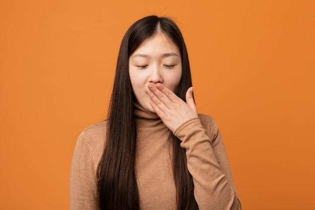 Молодая милая китайская женщина зевая показывающ утомленный жест покрывая рот с его рукой.