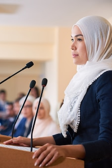 Young pretty confident muslim female delegate in hijab standing by tribune while making speech for foreign partners or colleagues