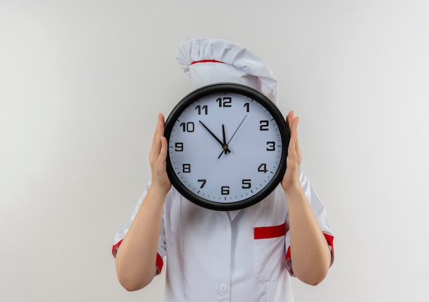 Giovane cuoco grazioso in uniforme del cuoco unico che tiene l'orologio e che si nasconde dietro esso