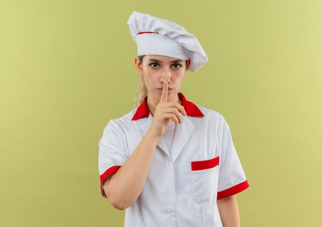 Молодой симпатичный повар в униформе шеф-повара жестикулирует, глядя изолированно на зеленом фоне