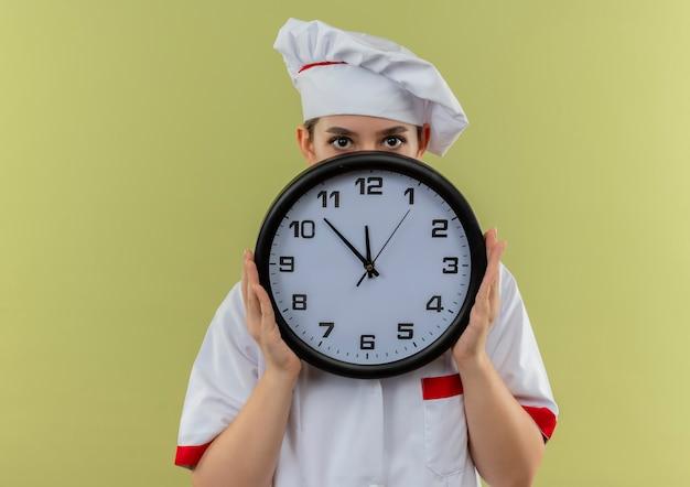 緑の背景で隔離の時計の後ろに保持し、隠れているシェフの制服を着た若いかわいい料理人