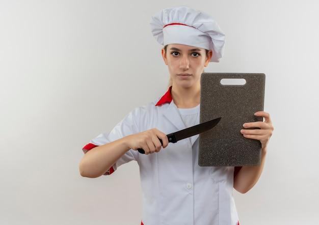 まな板を持ってナイフで指さし、見てシェフの制服を着た若いかわいい料理