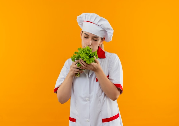 レタスを持って嗅ぐシェフの制服を着た若いかわいい料理人