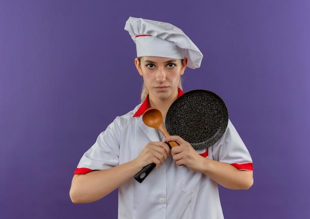 Молодой симпатичный повар в униформе шеф-повара, держащий сковороду и ложку