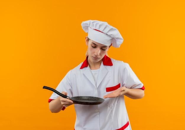 Молодой симпатичный повар в униформе шеф-повара смотрит и показывает на сковороду