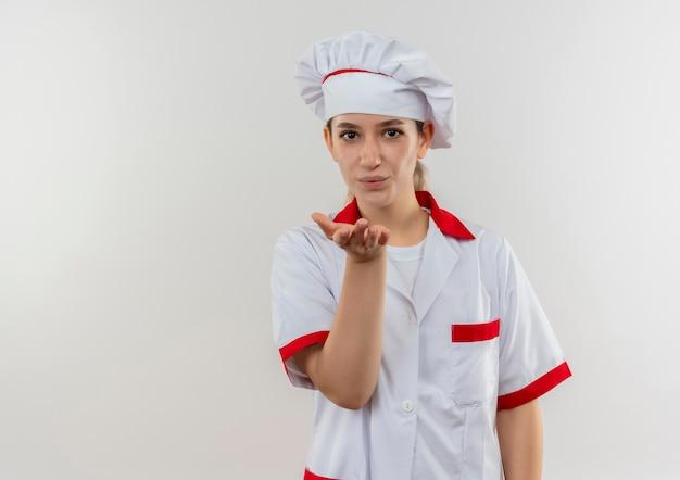 シェフの制服を着た若いかわいい料理人がブローキスを送る