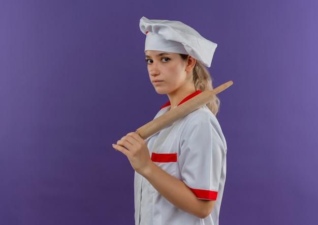 프로필보기에 서서 롤링 핀을 들고 요리사 유니폼에 젊은 예쁜 요리사